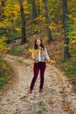 Lancer heureux de femme vers le haut des feuilles d'automne Image stock