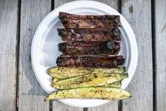 Lances grillées de courgette de barbecue dans le plat de portion sur le Tableau en bois extérieur Images libres de droits