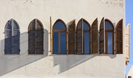 Lancet windows with wooden shutters on the white wall royalty free stock photography