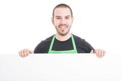 Lancez l'employé sur le marché souriant et tenant le grand carton publicitaire Photos libres de droits