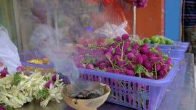 Lancez la stalle sur le marché avec les fleurs indoues rituelles dans la fumée banque de vidéos