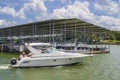Lancha de carreras de lujo con el floatie rodado en la parte posterior en el lago en el verano que pasa por el muelle cubierto de imagen de archivo