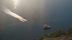 Lancha de carreras que flotan y que navegan en el mar picado con la vista del puerto en distancia metrajes