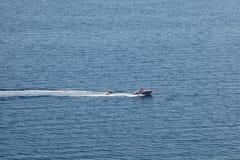 Lancha de carreras que tira de los barcos inflables del buñuelo Fotografía de archivo libre de regalías