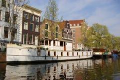 Lanchas a remolque y casas de Amsterdam Imagen de archivo libre de regalías