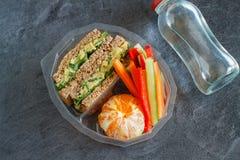 Lancheira com sanduíche, vegetais, água e frutos no quadro preto Fotografia de Stock Royalty Free