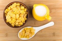 Lanci con i fiocchi di mais, la brocca di latte ed il cucchiaio della plastica Fotografia Stock