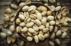 Lanci con i pistacchi salati in una ciotola di legno su un fondo delle coperture, la vista superiore, fine su fotografia stock