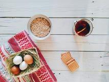 lanci con la farina d'avena, una tazza di tè, biscotti e le uova si trovano sui bordi bianchi Fotografie Stock