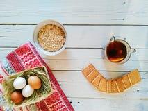 lanci con la farina d'avena, una tazza di tè, biscotti e le uova si trovano sui bordi bianchi Fotografia Stock Libera da Diritti