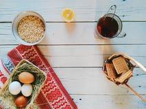 lanci con la farina d'avena, una tazza di tè, biscotti e le uova si trovano sui bordi bianchi Fotografia Stock
