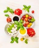Lanci con la mozzarella, i pomodori, il basilico, il petrolio e l'aceto, ingredienti per la fabbricazione dell'insalata Immagine Stock