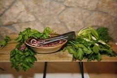 Lanci con le cipolle all'aceto e le tenaglie d'acciaio della coltelleria e le erbe commestibili su un supporto di legno dello sca Fotografie Stock Libere da Diritti