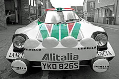 Lancia sponsored racing car. Photo of a lancia racing rally car with sponsorship red and green livery Royalty Free Stock Images