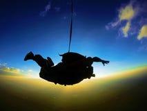 Lanciar in caduta liberasi la siluetta in tandem di tramonto Immagini Stock Libere da Diritti
