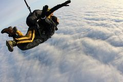 Lanciar in caduta liberasi in tandem I paracadutisti stanno volando sopra le nuvole bianche immagini stock libere da diritti