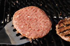 Lanciare gli hamburger sulla griglia Fotografia Stock