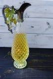 Lanciatore antico del vino con le foglie dell'uva e del vino bianco Immagini Stock Libere da Diritti