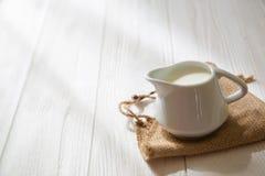 Lanciatore bianco del latte su un fondo di legno bianco Brocca di latte Immagine Stock Libera da Diritti