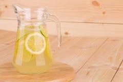 Lanciatore di vetro in pieno di limonata saporita fredda fresca Fotografia Stock