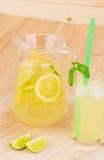 Lanciatore e di vetro in pieno di limonata saporita Immagini Stock