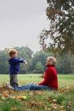 lancio dei fogli del bambino di autunno Fotografie Stock Libere da Diritti