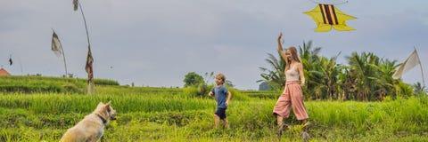 Lancio del figlio e della mamma un aquilone in un giacimento del riso in Ubud, INSEGNA dell'isola di Bali, Indonesia, FORMATO LUN fotografia stock libera da diritti