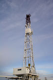 Land-based steel rig. Upright view of a white land-based oil or gas rig drilling for fuel Stock Photos