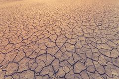 Land is covered with cracks as a symbol of drought, extreme weather conditions or as a background. Toned image.  royalty free stock images
