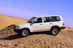 Land Cruiser in desert.. Land Cruiser in desert parked on hill overlooking sand dunes. Horizontal orientation Stock Images