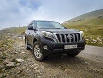 Car SUV in the mountains. Land Cruiser Prado car SUV in the mountains with rain royalty free stock photos