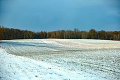 Land in a cultivated field covered with winter white snow with nowhere left with bare clods of brown soil and cloudy sky pretendin. A winter landscape with the Stock Image