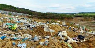 Land dat met plastic zakken en afval wordt verontreinigd Stock Afbeelding