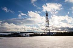 Land des verschneiten Winters mit Übermittlern und Antennen auf Telekommunikation ragen hoch Stockbild