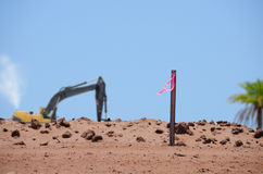 Land development flag post with bulldozer. Closeup of a land development flag post in a dirt mound with a working bulldozer in the background Stock Photo
