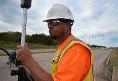 Land-Feldmesser In Safety Gear, das auf der Autobahn arbeitet Stockfotos