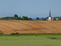 Land of fields cultivated. Spring soil fields cultivated with church steeple in the background Stock Images