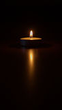 In a land of gloom a light has shone. Tealight candle on a dark background stock image