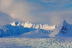 Land of ice. Travelling in Arctic Norway. White snowy mountain, blue glacier Svalbard, Norway. Ice in ocean. Iceberg in North pole Stock Photography