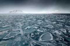 Land of ice. Winter Arctic. White snowy mountain, blue glacier Svalbard, Norway. Ice in ocean. Iceberg in North pole. Black clouds. On sky Stock Photo