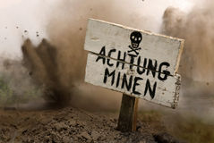 Land Mines Ahead. German warning sign from World War Two with explosions in the background royalty free stock photo