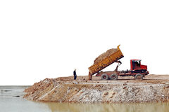 Land Reclamation. A rugged earthwork tipper lorry dumping dirt into a pond, isolated against white Royalty Free Stock Image