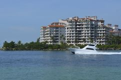 Land and Sea Luxuries. A white sport fishing boat cruising by luxury condominiums on Fisher Island,Miami Beach,Florida Stock Images