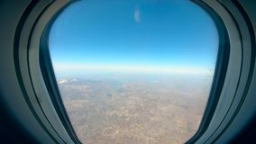 The land is seen from the airplane porthole. HD stock footage