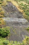 Land Slide. Unstable land has a net to catch any more lose rock Stock Photography