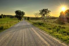 Land-Straße bei Sonnenuntergang Lizenzfreies Stockbild