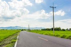 Land-Straßen mit Getreidefeld Stockfotografie