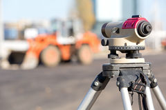 Land surveying equipment theodolite. At construction site on wheel loader machine background royalty free stock photo