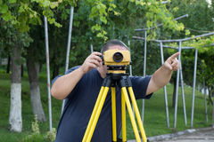 Land surveyor. Measuring with digital level device royalty free stock images