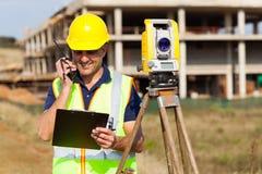 Land surveyor talking. Senior land surveyor talking on walkie talkie stock photo